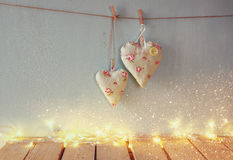 Image discrète d'image de Noël des coeurs de tissu accrochant sur la corde devant le fond en bois Rétro filtré Image stock
