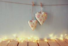 Image discrète d'image de Noël des coeurs de tissu accrochant sur la corde devant le fond en bois rétro filtré avec l'overl de sc Photos libres de droits