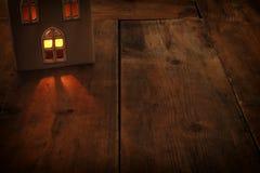 Image discrète de lanterne de maison avec la bougie brûlante et la lumière chaude dans les fenêtres au-dessus du vieux fond en bo Photo stock