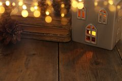 Image discrète de lanterne de maison avec la bougie brûlante et la lumière chaude dans les fenêtres au-dessus du vieux fond en bo Image stock