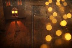 Image discrète de lanterne de maison avec la bougie brûlante et la lumière chaude dans les fenêtres au-dessus du vieux fond en bo Photos libres de droits