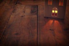 Image discrète de lanterne de maison avec la bougie brûlante et la lumière chaude dans les fenêtres au-dessus du vieux fond en bo Photos stock
