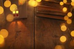 Image discrète de lanterne de maison avec la bougie brûlante et la lumière chaude dans les fenêtres au-dessus du vieux fond en bo Images stock