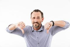 Displeased adult man showing thumbs down. Image of displeased adult man over white background. Looking camera showing thumbs down stock photography