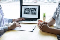 Image of doctor or dentist presenting with tooth x-ray film recommend patient in the treatment of dental and dentistry, working at. Workplace royalty free stock photo