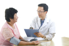 Image of a doctor and his nurse. Checking up a senior patient in the clinic Royalty Free Stock Images