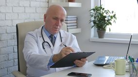 Doctor Specialist in Hospital Room Writing a Medical Prescription stock image