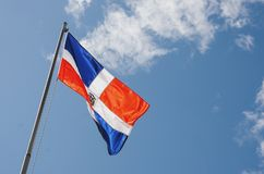 Image of the Dominican Republic flag with blue sky. And clouds background stock images