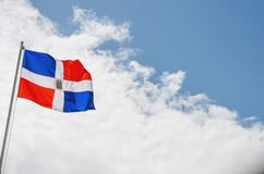 Image of the Dominican Republic flag with blue sky. And clouds background stock photos