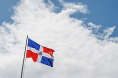 Image of the Dominican Republic flag with blue sky. And clouds background royalty free stock image