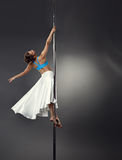 Image of dreamy woman dancing on pole in studio Stock Photo