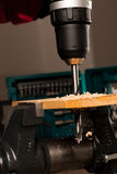Image of drilling hole in wood clamped in vice tool. Stock Photo