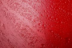 Image drops of a water on a red metal surface royalty free stock images