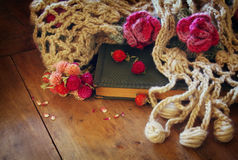 Image of dry flowers, warm scarf and old vintage book on wooden table. retro filtered image Royalty Free Stock Photo