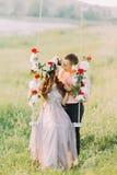 Image du bel dans-amour de couples embrassant sur l'oscillation d'arbre dehors Photographie stock