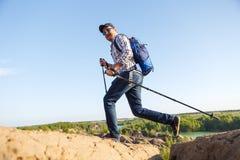 Image du jeune homme de touristes avec des cannes marchant dans la zone montagneuse Image stock
