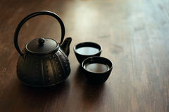 Image of eastern teapot and teacups on wooden desk Royalty Free Stock Images
