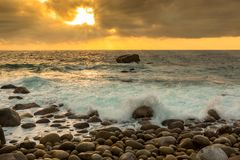 Nature Seascape with Eggshaped Rocks on A Wild Beach, Waves and Sun Rays at Dramatic Sunrise royalty free stock photo