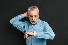 Image of elderly unshaved man 60s with grey hair wearing eyeglas. Ses looking at his wrist watch with confusion isolated over black background Royalty Free Stock Photos