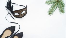 Image of elegant black and gold venetian, mardi gras mask on white snow background. Vintage photo. Christmas New Year carnaval royalty free stock photo