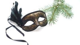 Image of elegant black and gold venetian, mardi gras mask on white snow background. Vintage photo. stock photos
