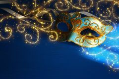 Image of elegant blue and gold venetian, mardi gras mask over bl. Ue background royalty free stock image