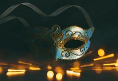 Image of elegant blue and gold venetian, mardi gras mask over dark background. Glitter overlay. Royalty Free Stock Photo