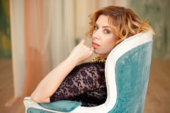 Image of elegant girl sitting in retro style armchair. Redhaired curly young model. Royalty Free Stock Photos