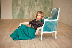 Image of elegant girl sitting in retro style armchair. Redhaired curly young model. Stock Photos
