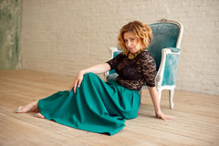 Image of elegant girl sitting in retro style armchair. Redhaired curly young model. Stock Photo