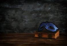 Image of elegant royal blue venetian mask over vintage old book in front dark wooden background. royalty free stock photos