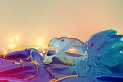 Image of elegant venetian mask over blue silk background. Stock Photos