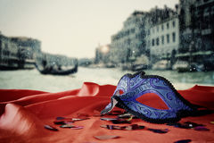 Image of elegant venetian mask on red silk fabric in front of blurry Venice background. Stock Image