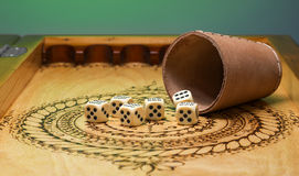 Image of elements of gambling on a carved wooden board ,figures five, green. Background Stock Photo