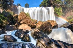 Nature Landscape with Blurred Majestic Waterfall, Rough Rocks and Rainbow in The Sunlight