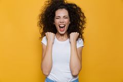 Image of emotional woman 20s with curly hair shouting and clench. Ing fists isolated over yellow background royalty free stock photography