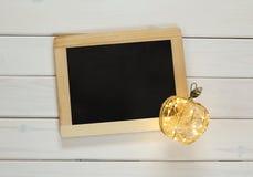 Image of empty blackboard and decorative gold apple Stock Photo