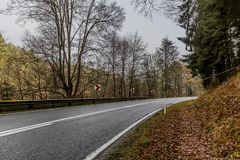 Image of a empty forest road with a curve between trees with dangerous curve signage. Beautiful image of a empty forest road with a curve between trees with royalty free stock photos