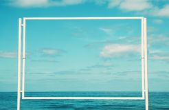 Image of empty white billboard on the beach infront of blue sea and the sky. For mockup and advertisement. Stock Photography