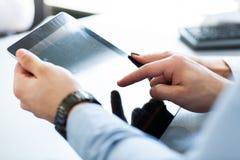 Image en gros plan d'un employé de bureau utilisant un comprimé pour analyser des données statistiques photo stock