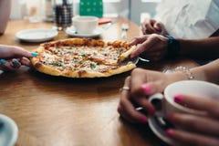 Image en gros plan de pizza délicieuse et de mains prenant des tranches dans le restaurant italien Photographie stock libre de droits