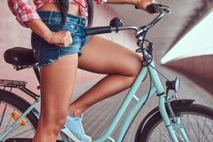 Image en gros plan des jambes femelles minces douces dans des espadrilles bleues près du vélo de ville Photos stock