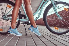 Image en gros plan des jambes femelles minces douces dans des espadrilles bleues près du vélo de ville Photographie stock libre de droits