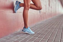 Image en gros plan des jambes femelles minces douces dans des espadrilles bleues, se penchant contre un mur rose Photo libre de droits
