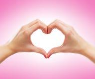 Image en gros plan des mains femelles dans une forme d'un coeur Images stock