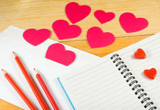 image of envelopes, notebooks, pencils, and paper hearts on a wooden table close-up Stock Photos