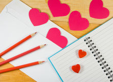 image of envelopes, notebooks, pencils, and paper hearts on a wooden table close-up Royalty Free Stock Photo