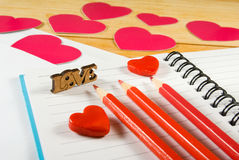 image of envelopes, notebooks, pencils, and paper hearts on a wooden table close-up Royalty Free Stock Photography