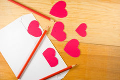 image of envelopes, notebooks, pencils, and paper hearts on a wooden table close-up Stock Photo