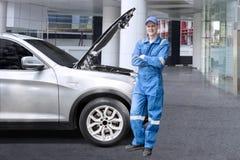 European mechanic standing near a broken car stock images
